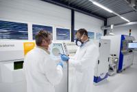 Zwei Mitarbeiter des Swiss m4m Center inspizieren ein Implantat aus einer Titanlegierung für die Beckenchirurgie. Bild: Swiss m4m Center